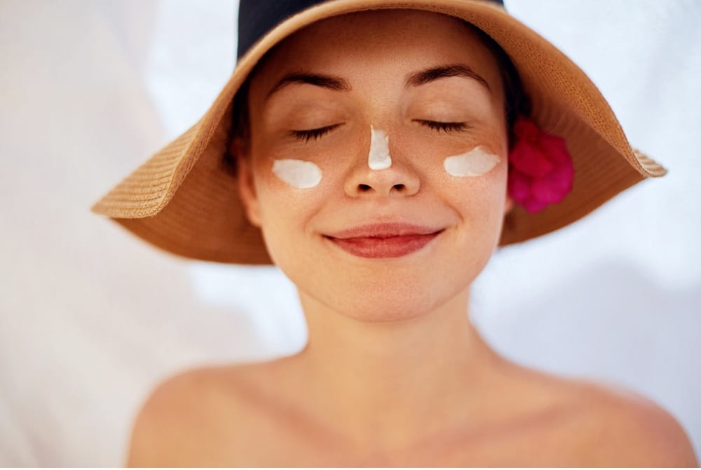 Woman smile applying sun cream